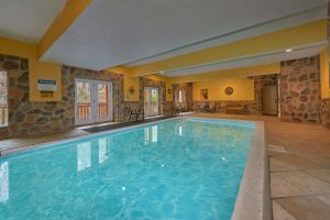 Pool and Theater Lodge is a massive eight bedroom rental cabin in Pigeon Forge. It offers and indoor pool, huge theater room, arcades and more