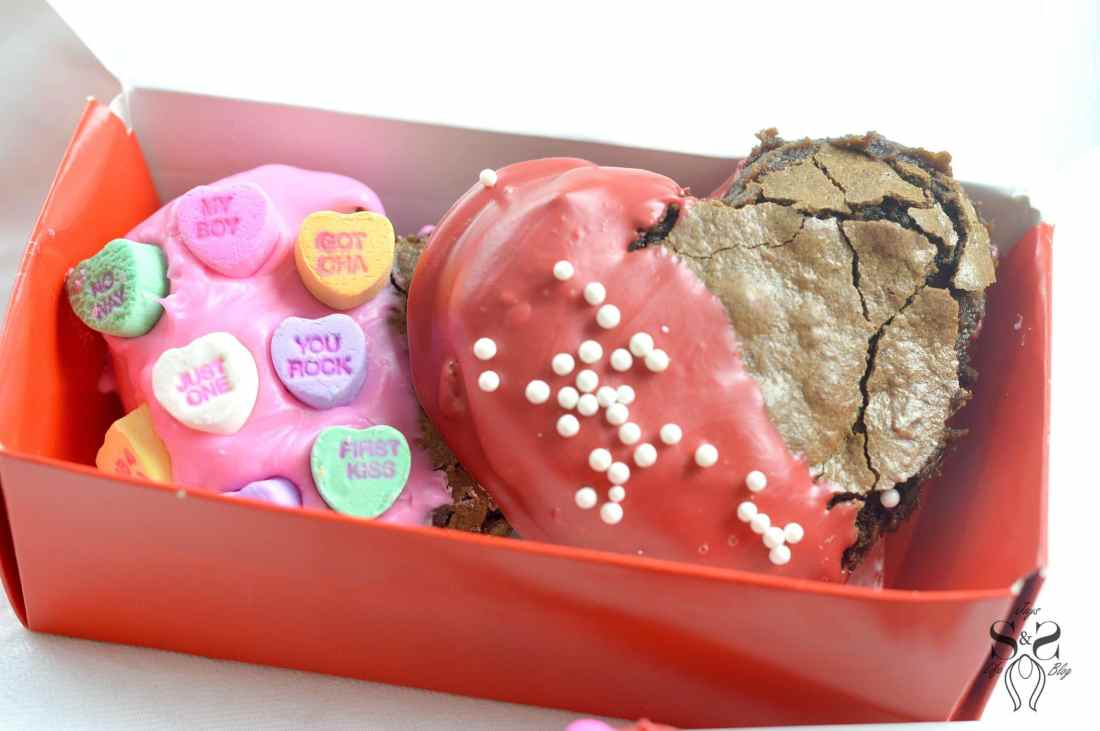 Valentine's Day Fudgy Brownies in box. A from-scratch Valentine's Day Fudgy Brownie recipe, stuffed with butterscotch chips. Dipped in chocolate and then topped with candy hearts and sprinkles.