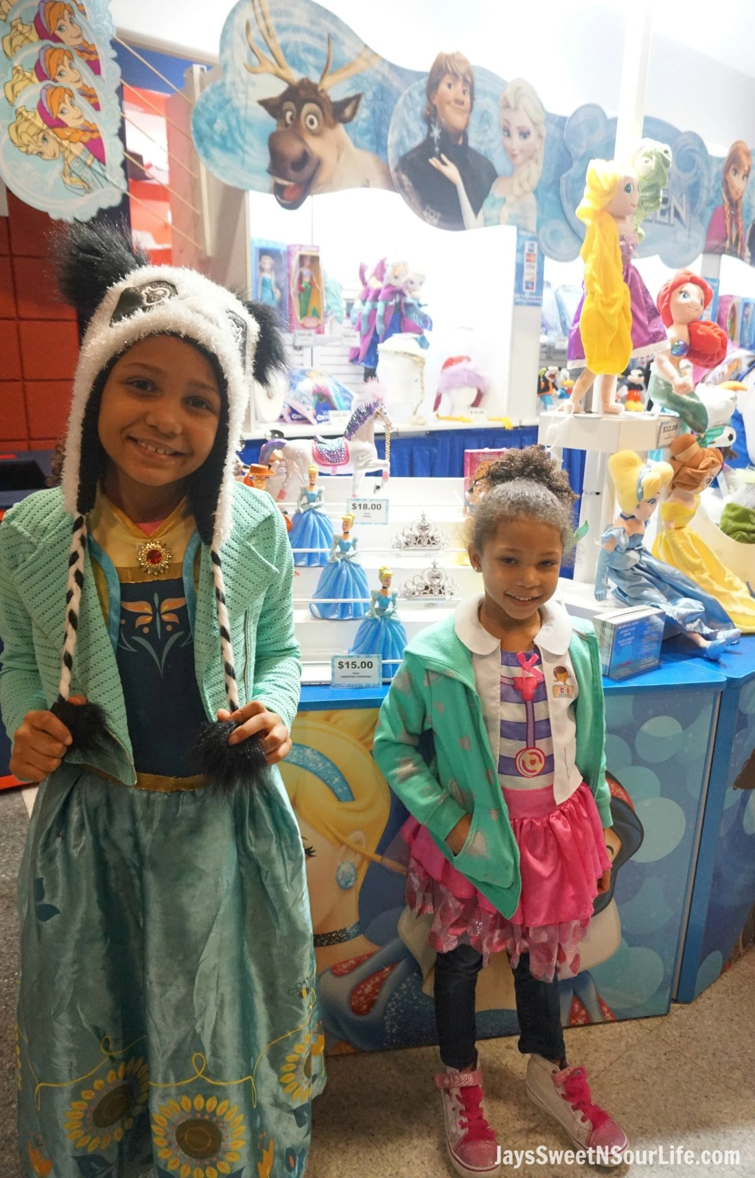 Disney On Ice Presents Frozen coming to a town near you. The girls standing in front of a Disney themed booth selling gifts from the movie Frozen and much more.