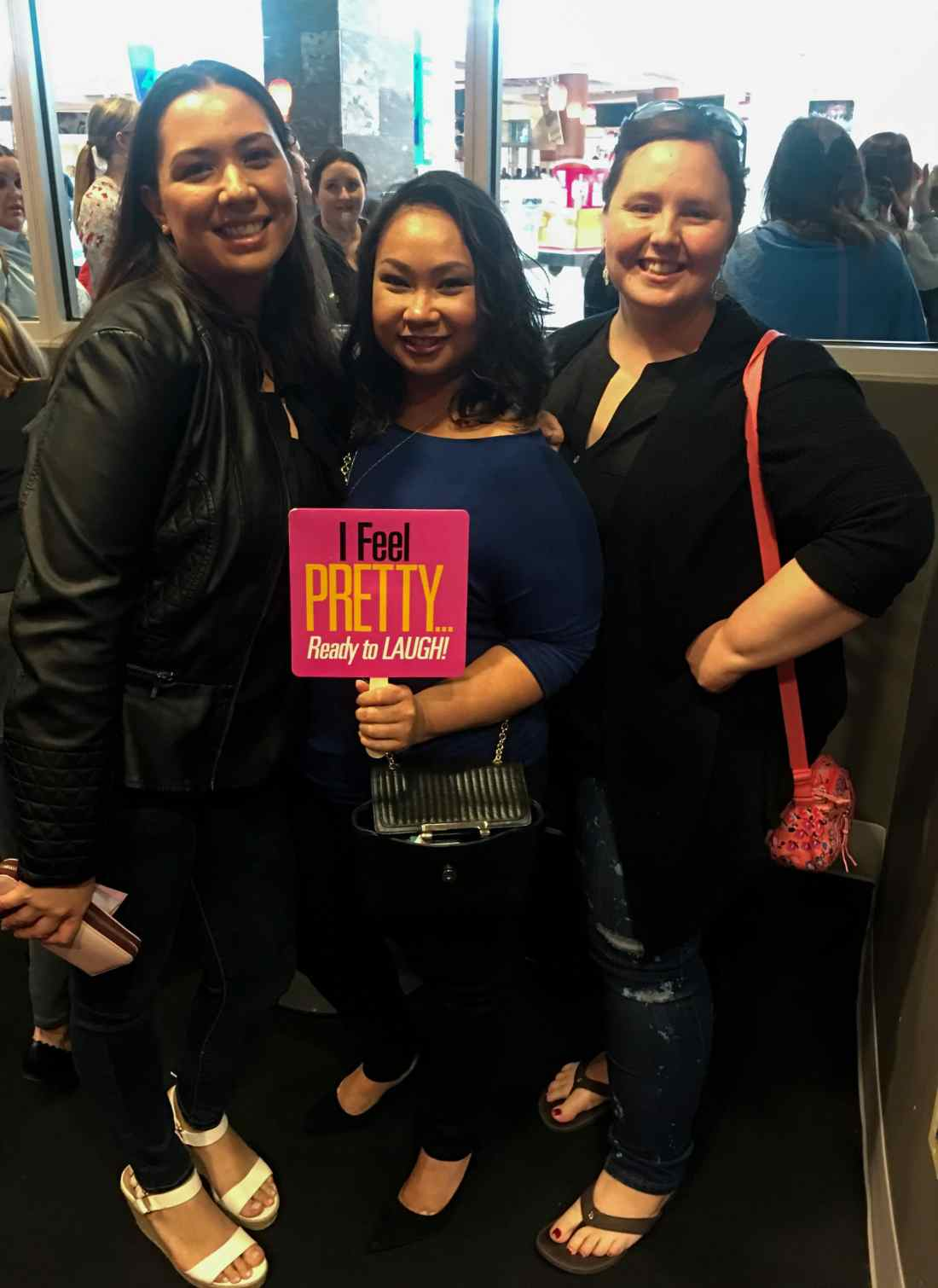 Three women holding a I Feel Pretty Film sign. The I Feel Pretty Film is in theaters everywhere today.