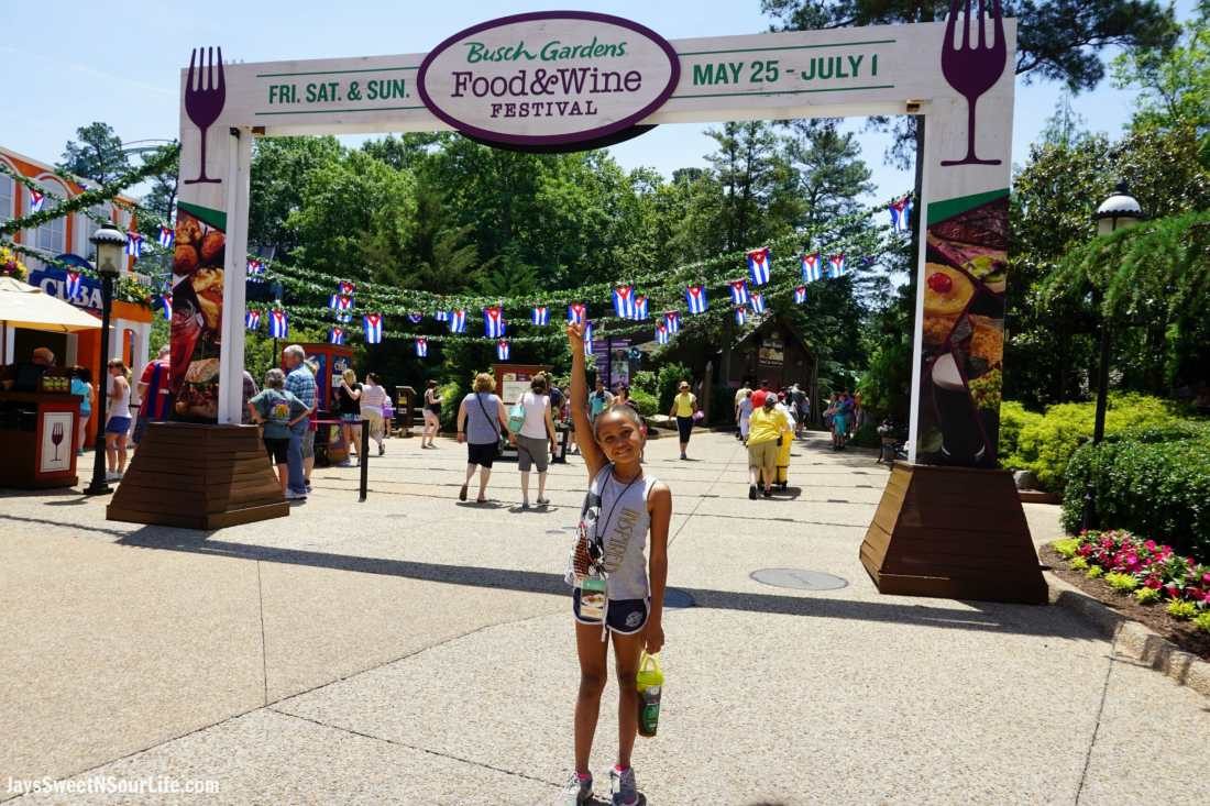 African American Girl pointing to 2018 Busch Gardens Food and Wine Festival sign. Food & Wine Festival is from 11 am to close every Friday, Saturday and Sunday, May 25 - July 1.