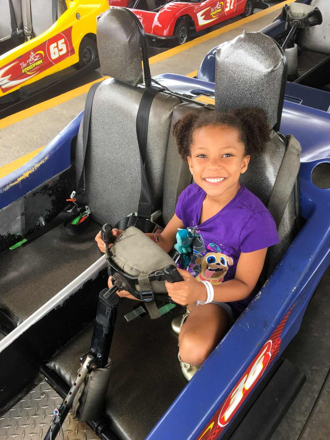 SpeedPark - Visit Cabarrus County African American GIrl In Car Smiling. Read more about our Racing Good Time at The Speedpark in Concord Mills North Carolina.