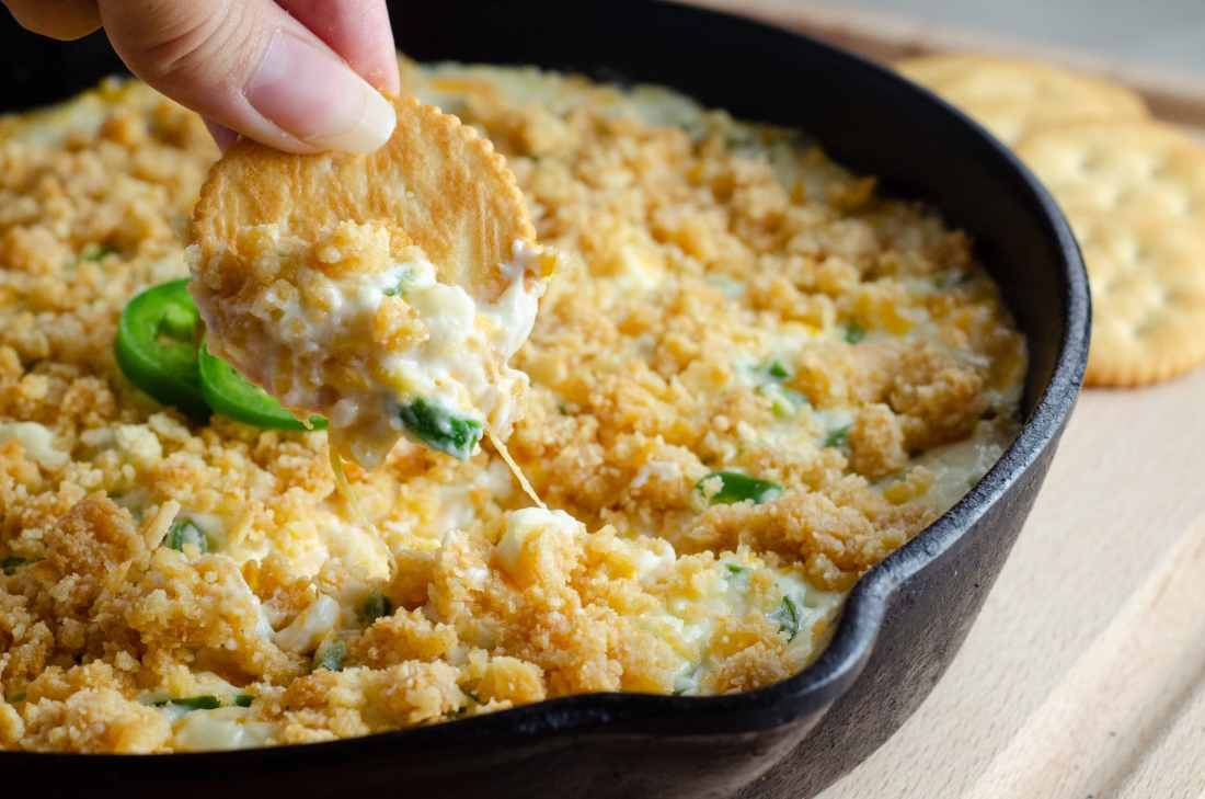 Jalapeño Popper Dip on Cracker over Pan. Elevate your holiday entertaining with some wholesome, flavorful California cheeses in this easy to make Jalapeño Popper Dip.