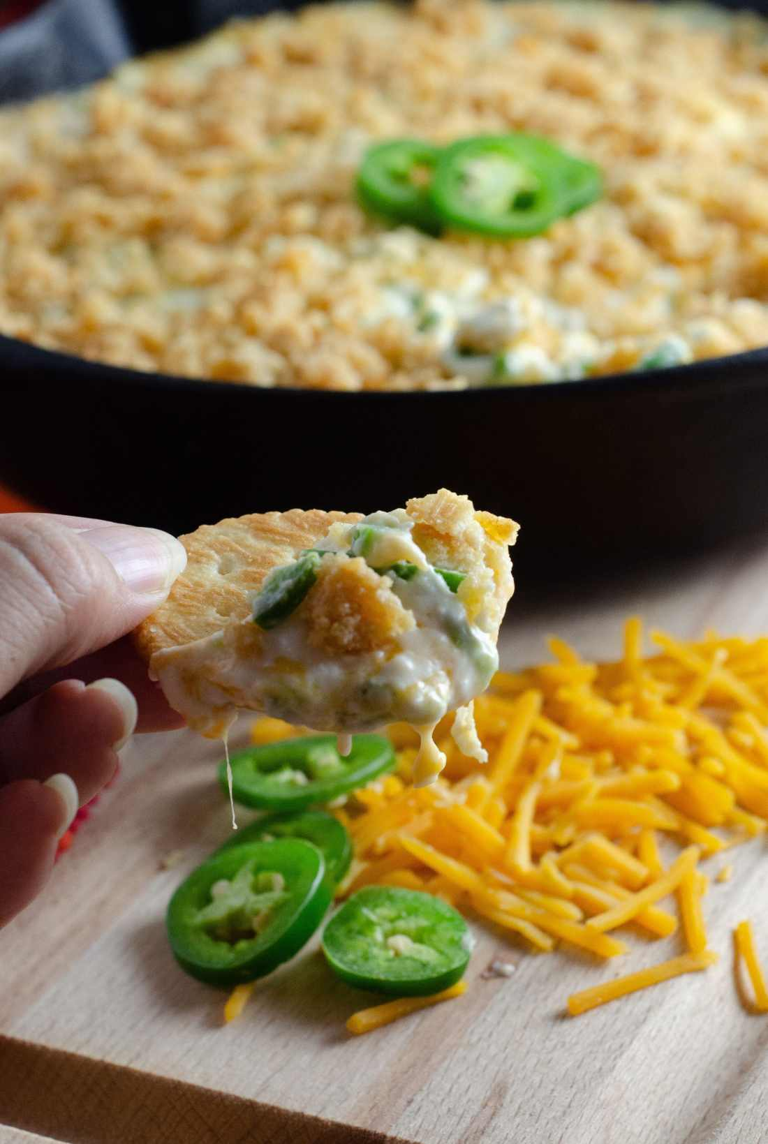 Jalapeño Popper Dip on Cracker Closeup. Elevate your holiday entertaining with some wholesome, flavorful California cheeses in this easy to make Jalapeño Popper Dip.