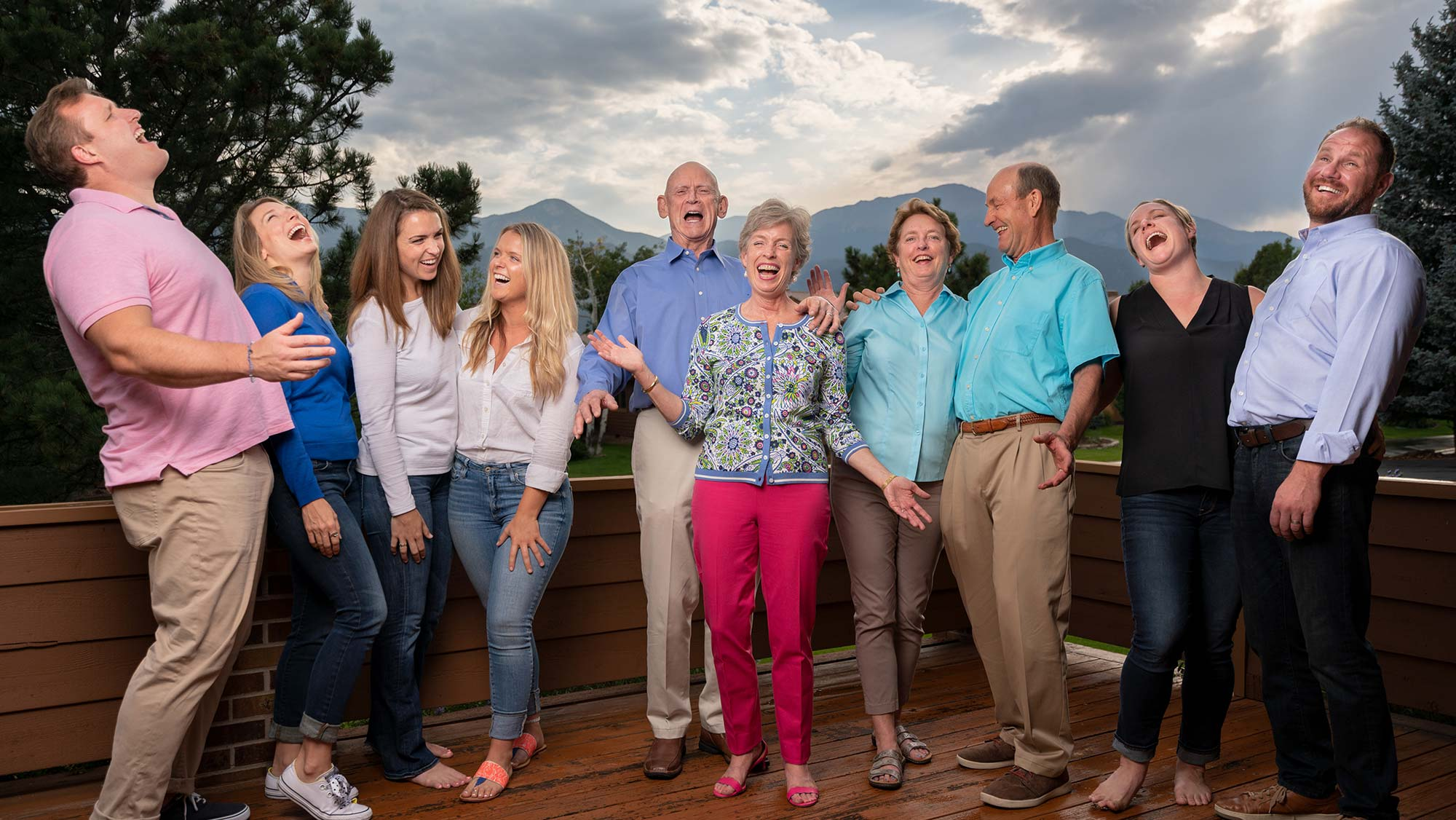 Large family laughs and bellows together in a big family portrait