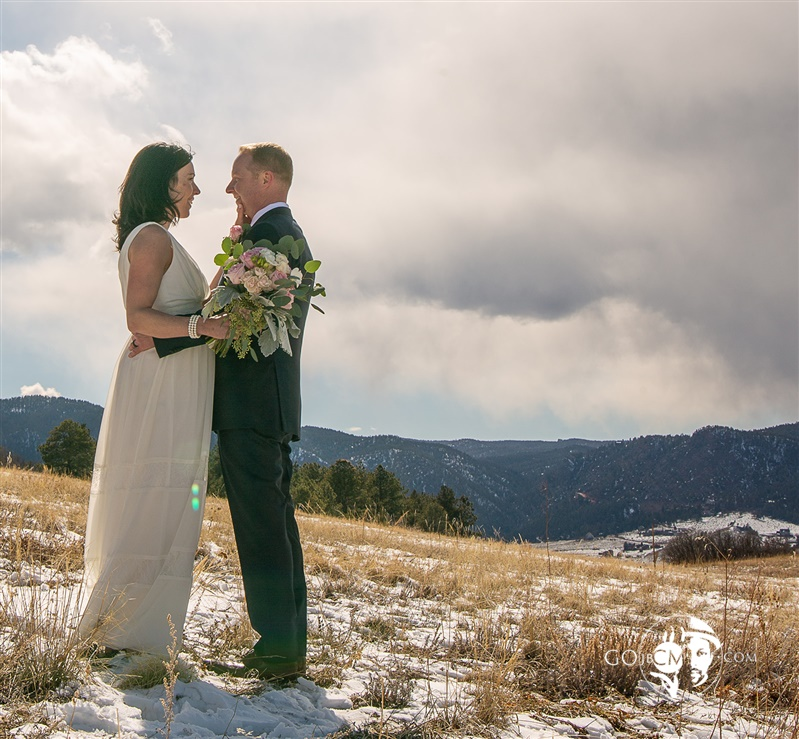 Wedding picture of couple in snowy valley in Colorado Springs trail looking into each other's eyes