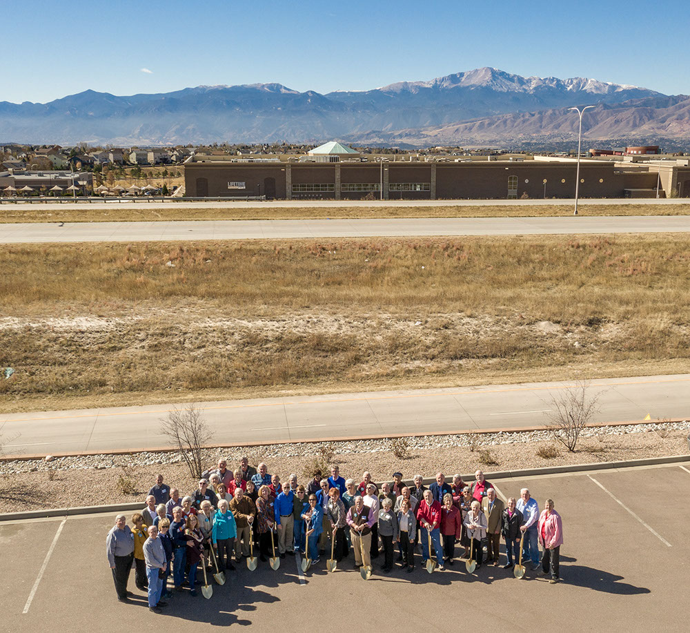 Aerial view of ground breaking ceremony for senior living housing with Pikes Peak mountain range in background