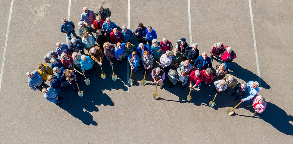 Aerial picture of senior citizens at a ground breaking ceremony with golden shovels in Colorado Springs