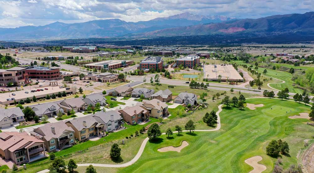 Drone view of Colorado Springs golf course neighborhood with Pikes Peak in the background
