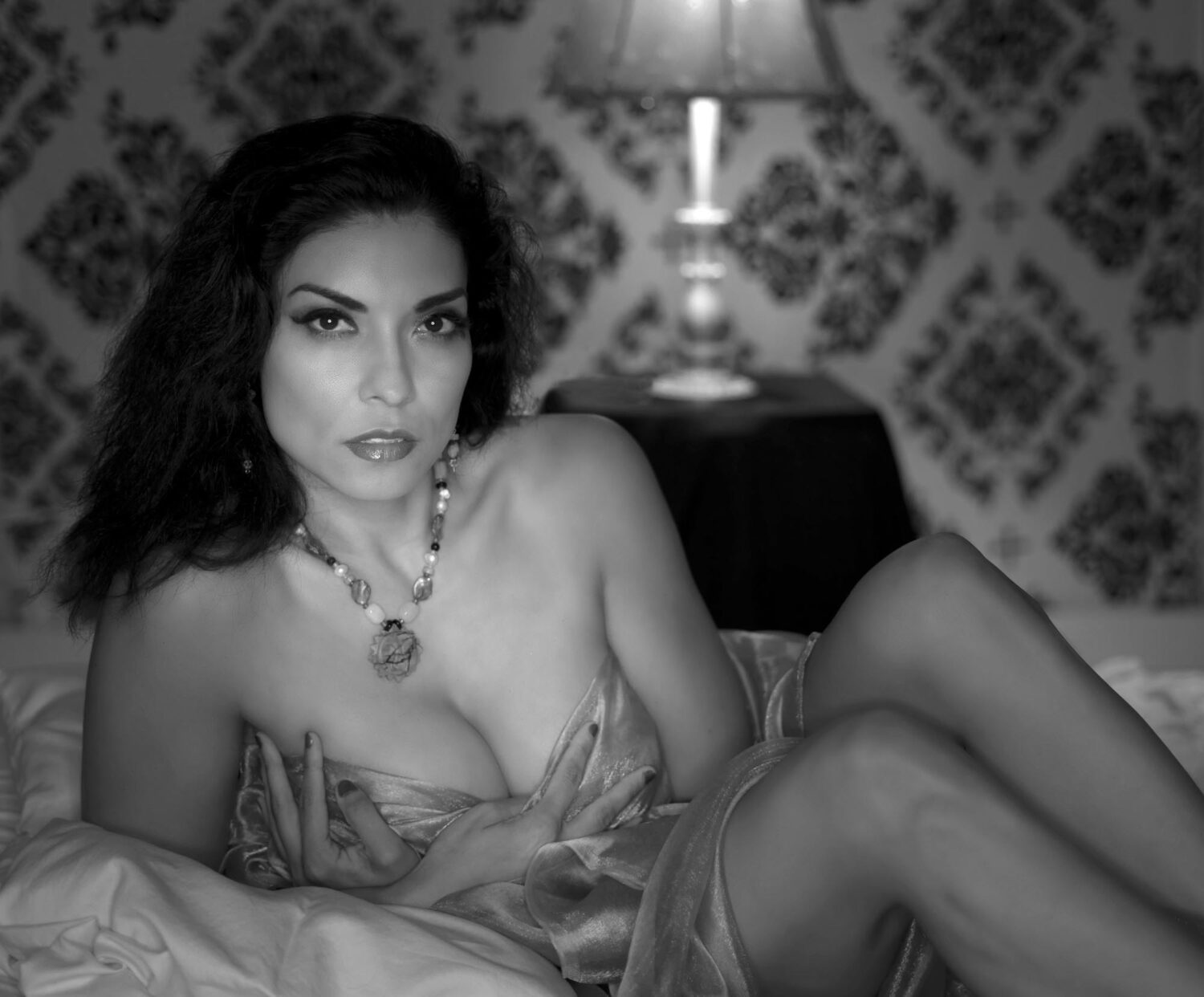Sensual Latina woman waiting on her bed for that special someone to arrive