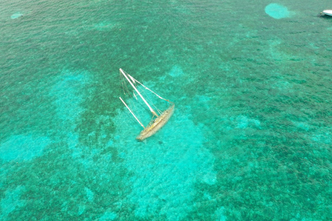 drone shot of a sunken sailboat in crystal clear water in the St Croix harbor