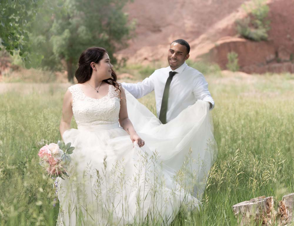 Mixed race couple posing for wedding pictures in a local Colorado Springs park