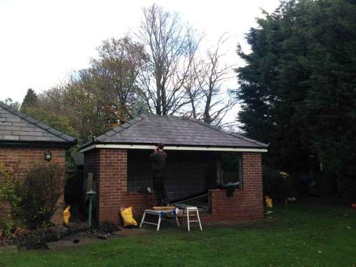 Picture of final stages of an outhouse roofing project.