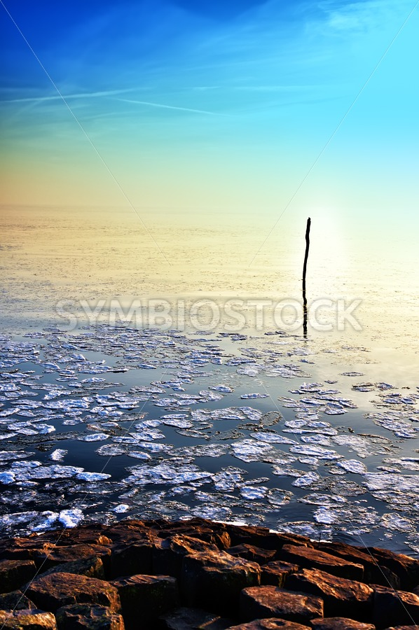Sun going down in calm frozen lake