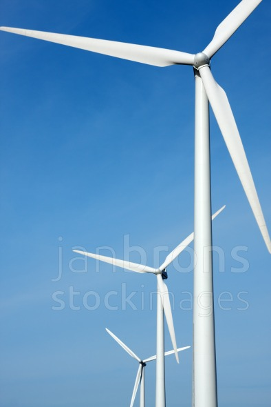 Three mighty windmills in a row against a blue sky.