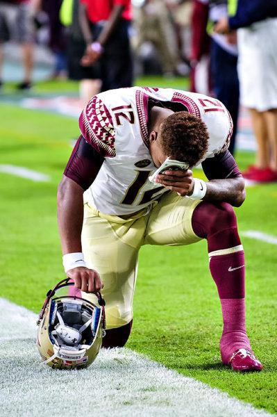 Florida State QB, Deondre Francois, prays before the game