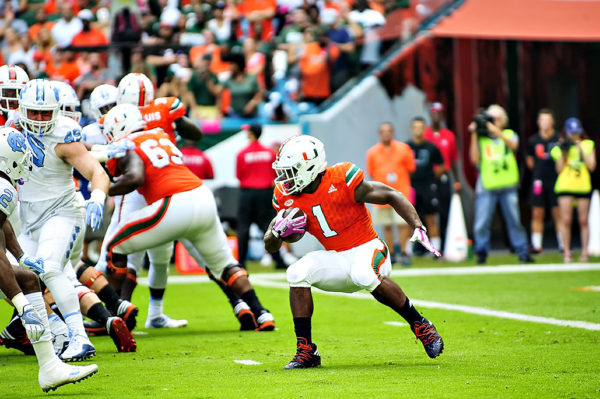 Hurricanes RB, Mark Walton, stops and cuts as he tries to find a hole to run through