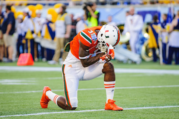 Stacy Coley, Miami Hurricanes WR, take a knee in prayer prior to the conclusion of warmups