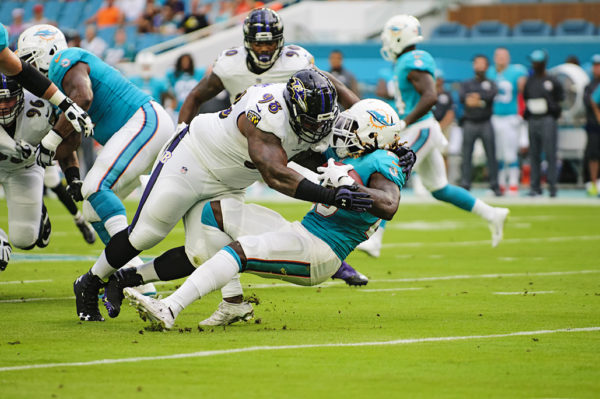 Brandon Williams, Ravens DT #98, stuffs Dolphins RB #23, Jay Ajayi, for a loss