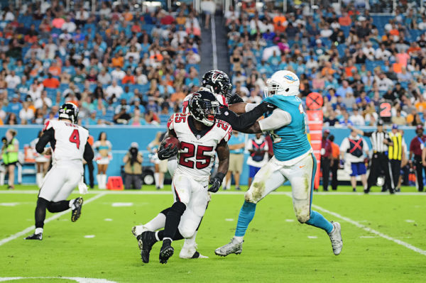 Falcons RB, #25 Brian Hill, looks to cut outside as he rushes the ball