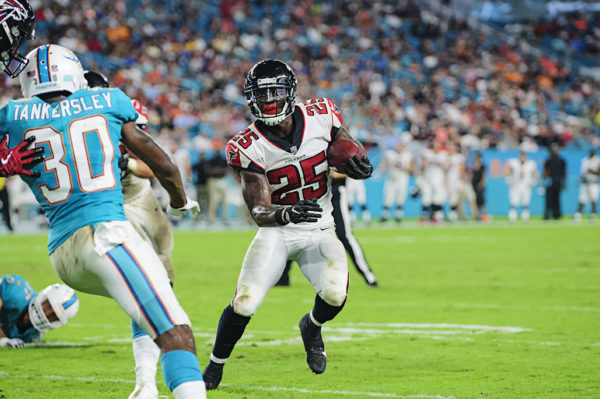 Falcons RB, #25 Brian Hill, looks to run outside to avoid be tackled