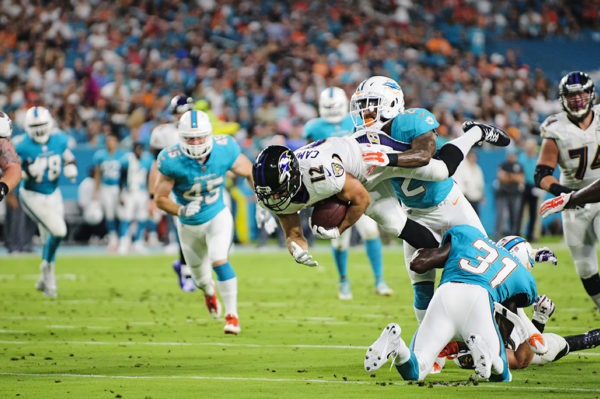Ravens WR #12, Michael Campanaro, gets tackled mid-air by Dolphins S #22, T.J. McDonald
