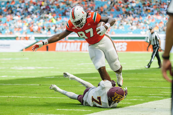 Hurricanes TE, Michael Irvin II tries to leak over a tackle