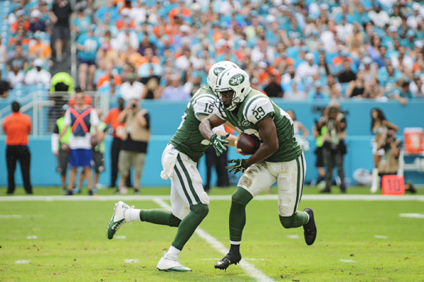 Josh McCown (15) hands the ball off to Bilal Powell (29)
