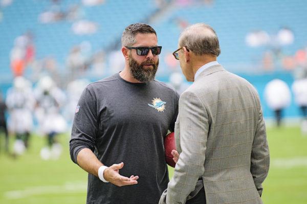 Defensive Coordinator, Matt Burke, speaks with owner Stephen Ross