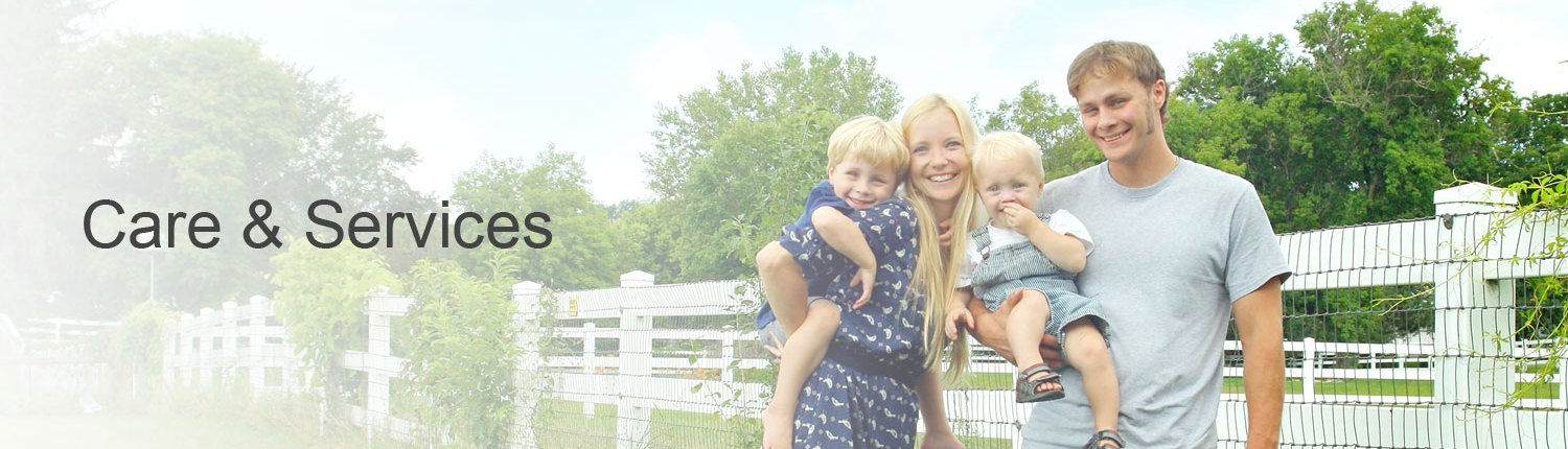 Young family standing beside fence