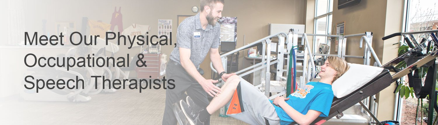 Physical therapist assisting teenage boy with leg exercises