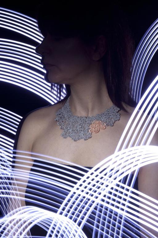 A picture of  white woman wearing a strapless dress and a lace necklace. The background is dark but streaked with light