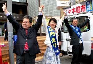 集まった支持者の声援にこたえる(左から)小池氏、山内区議候補、佐々木区長候補=21日、東京都板橋区