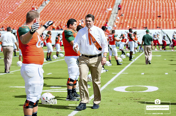 Miami coach Al Golden greets his players at stretching