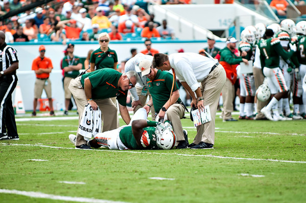 Miami head coach, Al Golden, looks in on injured player #92, Courtel Jenkins