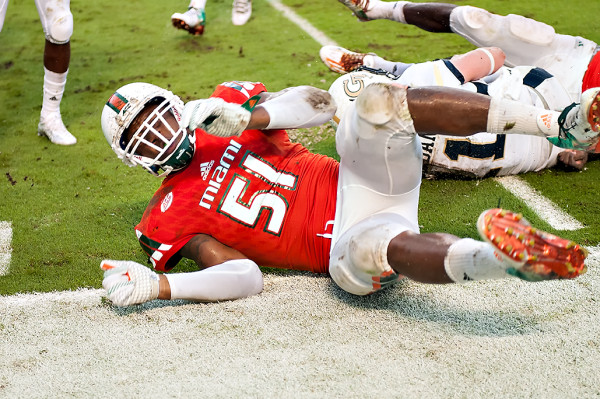 Miami lineback Juwon Young slides towards me after making a tackle