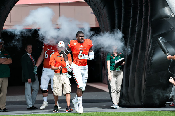 Herb Waters runs through the smoke on Senior Day