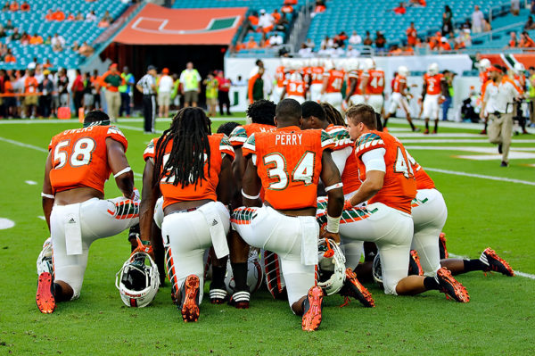 Hurricanes linebackers take a knee to listen to their coach Manny Diaz