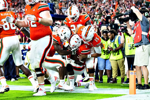 Mark Walton and Brad Kaaya help Stacy Coley celebrate his touchdown