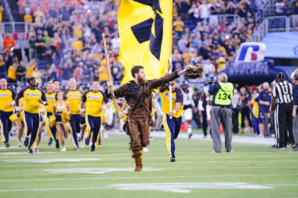 The West Virginia Mountaineers mascot leads the team onto the field