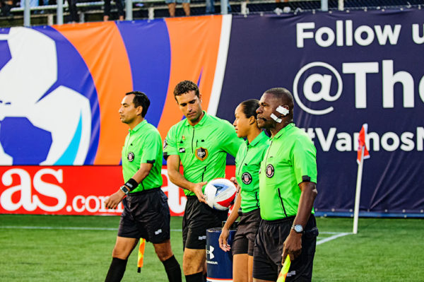 The referee picks up the ball