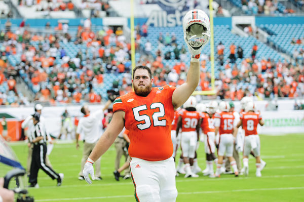 Hurricanes offensive linemen KC McDermott raises his helmet to the crowd