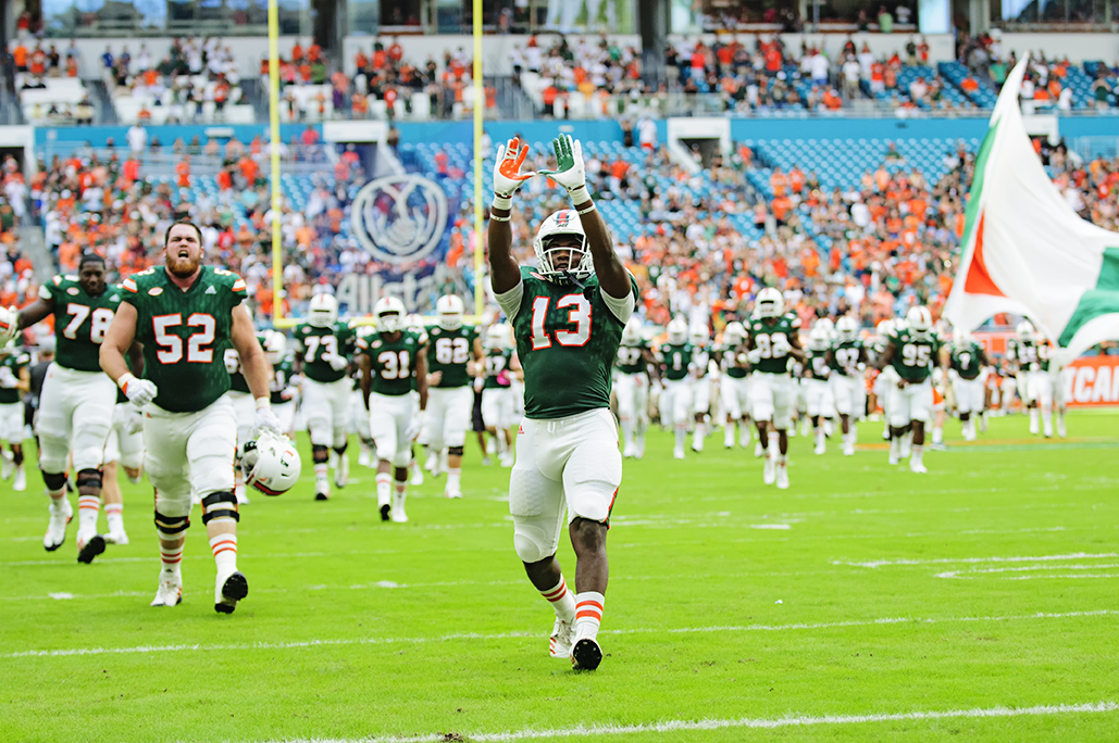 "DeeJay Dallas throws up the ""U"" as the team runs onto the field"