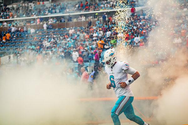 Dolphins quarterback, Jay Cutler, runs through the smoke