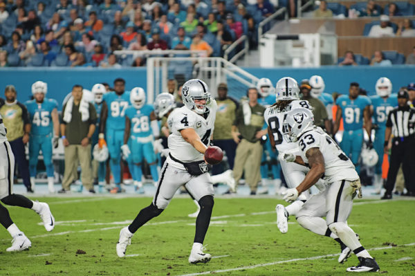 Derek Carr (4) hands off to DeAndre Washington (33)