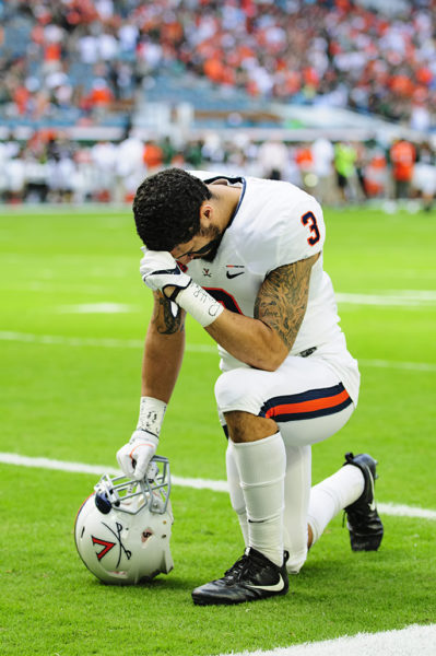 Quin Blanding (3) takes a knee prior to the game