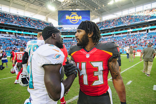 TJ Ward (43) greets Michael Thomas (31) after the game