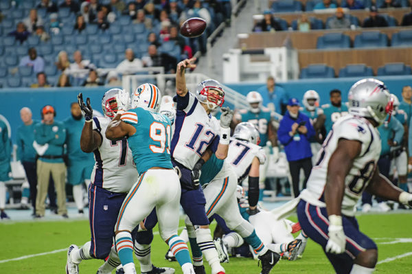 Tom Brady throwing with Cameron Wake (91) applying pressure