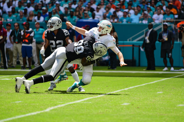 Oakland Raiders defensive end Arden Key (99) hits Miami Dolphins quarterback Ryan Tannehill (17) as he throws