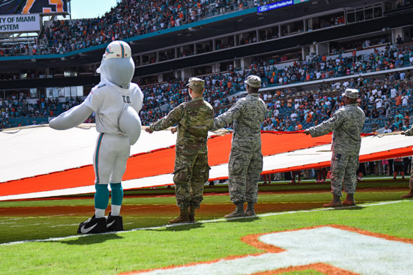 TD and soldiers from the Armed Forces hold the flag during the National Anthem